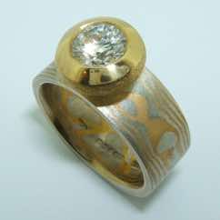 Wide platinum and 22k gold mokume gane band with a brilliant cut diamond in a 22k gold pod rubover setting