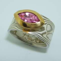 18k white gold and silver mokume gane wide flat band with a marquise cut pink sapphire in a 22k gold rub-over boat setting. POA.