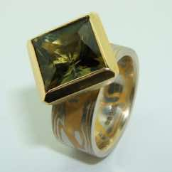 Platinum and 22k gold mokume gane flat band with a square olive green tourmaline in a 22k gold box pod setting. POA.