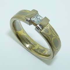 18k white and yellow gold mokume gane 5mm flat band with a princess cut diamond in an 18k white gold double bar setting