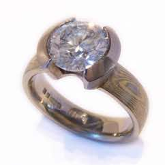 18k white and yellow gold mokume gane court band with brilliant cut diamond in 18k white gold open tapered rubover setting