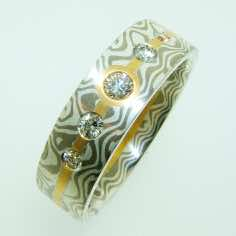18k white gold and silver mokume gane flat ring with a five brilliant cut diamonds set in 22k gold strip.<br/><br/>£POA