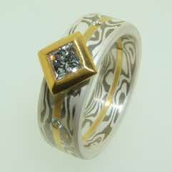 18k white gold and silver mokume gane flat band with 22k gold central strip and a princess cut diamond in a 22k gold box setting