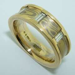 18k white and yellow gold mokume gane flat band with 18k yellow gold rails set with 3 small baguette diamonds