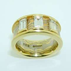 18k white and yellow gold mokume gane wide flat band with 18k yellow gold rails set with 3 baguette diamonds