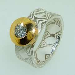 18k white gold and silver mokume gane band with a brilliant cut diamond in a 22k gold 'crown' setting with small flush set diamonds