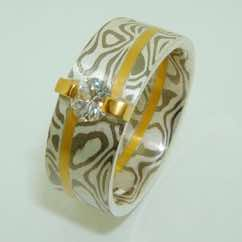 18k white gold and silver mokume gane band with 22k gold offset strip detail and with a brilliant cut diamond in a 22k gold bar setting
