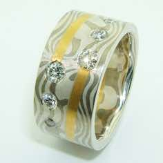 18k white gold and silver mokume gane wide ring with 22k gold spiral detail and flush set with 2x10pt, 2x6pt and 2x3pt brilliant cut diamonds.<br/><br/>£POA